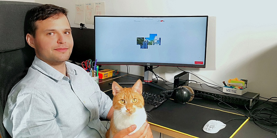 Young man in white shirt with cat on his lap at computer workstation..