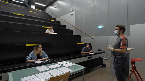 Studierende in einem Hörsaal, Vortragender trägt einen Mund-Nasen-Schutz