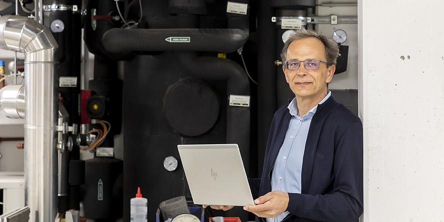 René Rieberer steht in seinem Labor und hält einen Laptop in der Hand. Hinter ihm sind schwarze Rohre zu sehen.