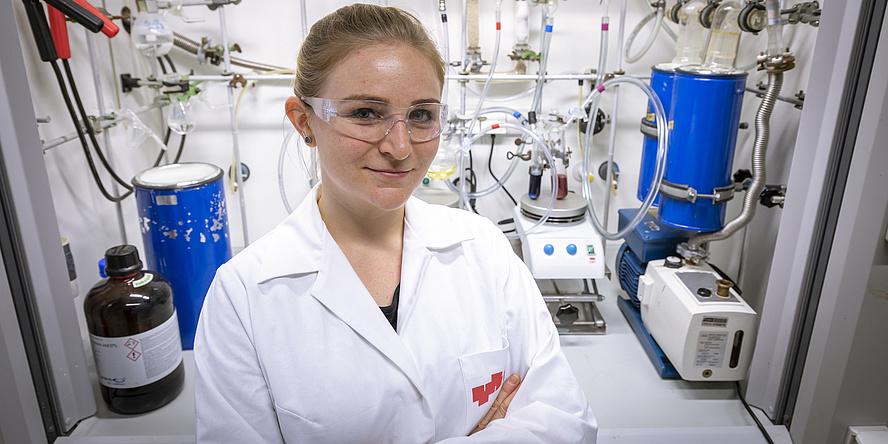 Eine junge Frau mit blonden Haaren steht vor einer Laborbox, in der sich Kabel und Reagenzgläser befinden. Sie trägt einen weißen Labormantel, eine Schutzbrille und hat die Hände verschränkt.