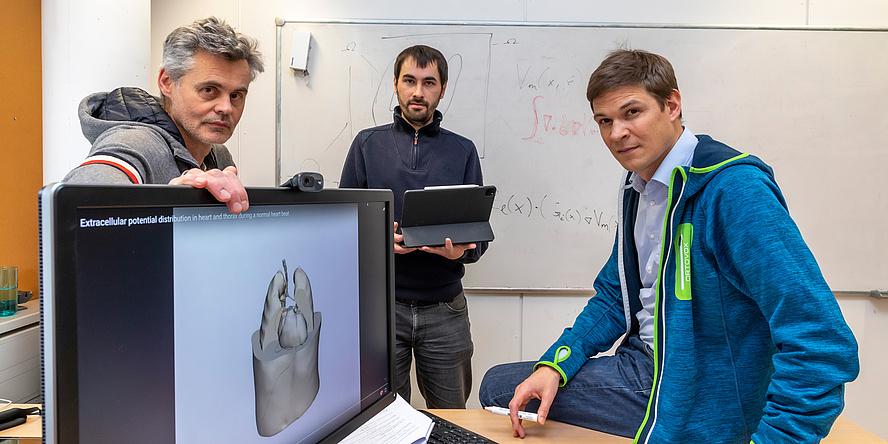 Drei Herren vor einem Computerbildschirm, ein digitales Herz ist abgebildet