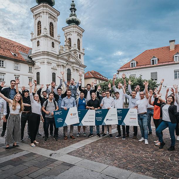 Junge Leute stehen jubelnd auf einem Platz in einer Stadt.