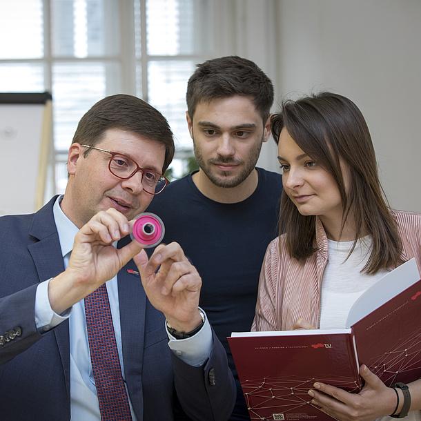 Ein Lehrender erklärt zwei Studierenden ein kleines rundes Objekt.