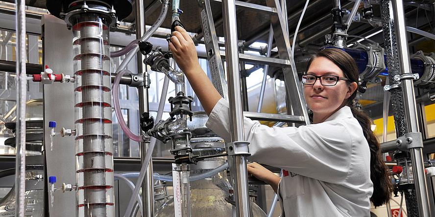 Eine junge Frau mit braunen Haare und Labormantel schaut in die Kamera und greift auf eine Anlage mit vielen Röhren und Behältern.