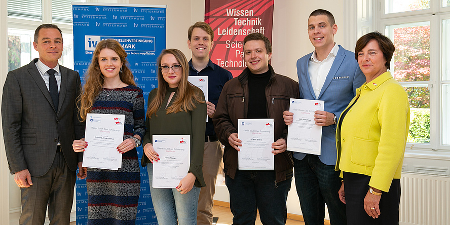 A group of five scholarship holders hold their scholarship certificates in the camera and are flanked by representatives of the sponsors.