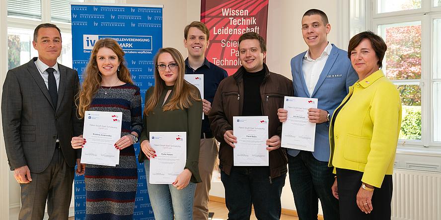 Eine Gruppe von fünf Stipendiatinnen und Stipendiaten halten ihre Stipendien-Zertifikate in die Kamera und sind flankiert von Vertreter/innen der Förderer.