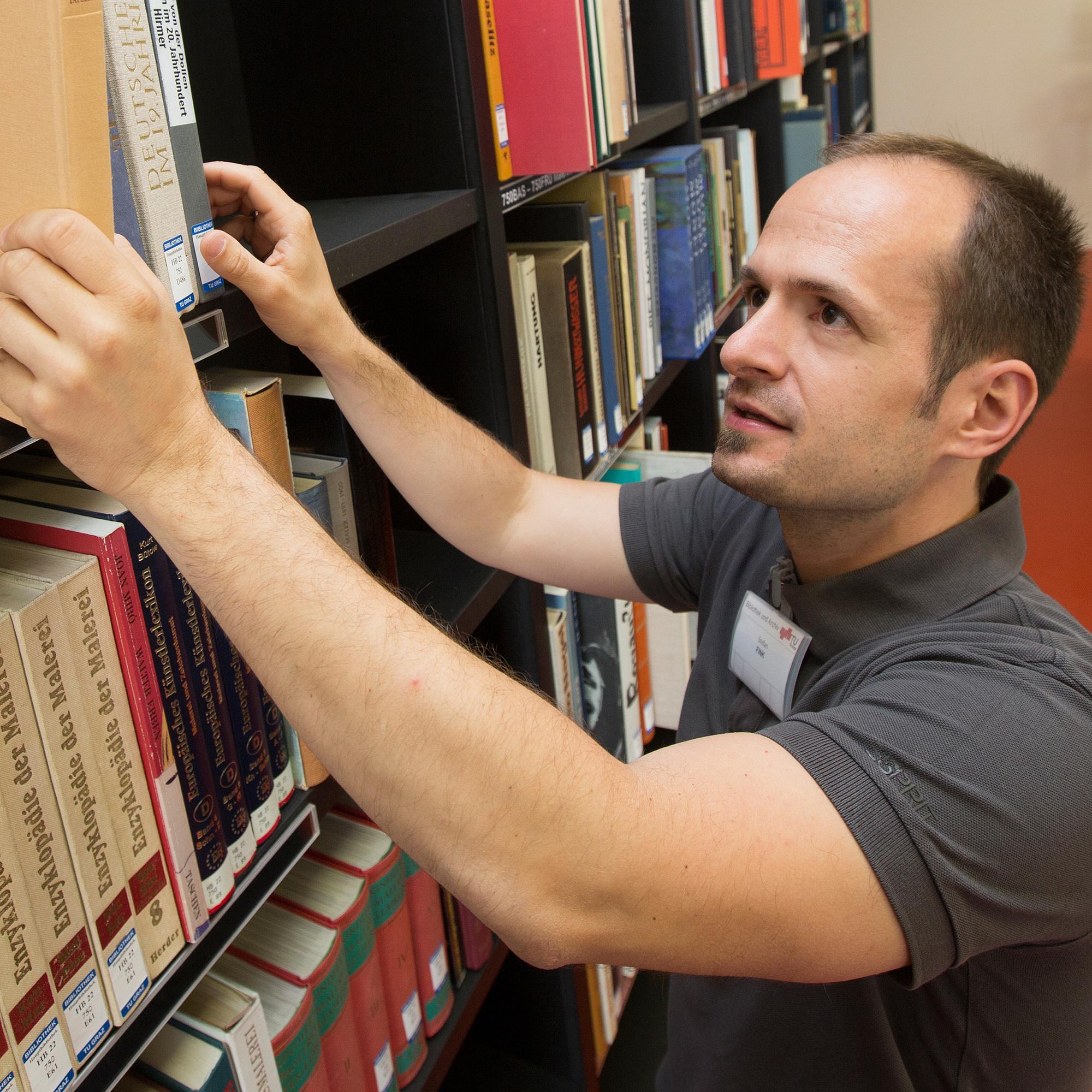 Ein Mann nimmt ein Buch aus einem Bücherregal