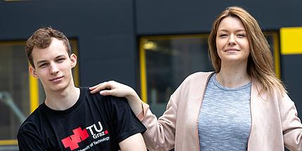 Junger Mann mit schwarzem Shirt mit großem rotem TU Graz-Logo links neben einer jungen Frau mit grauem Shirt und lachsfarbenem Cardigan. Beide blicken direkt in die Kamera, ihre Hand liegt auf seiner Schulter.