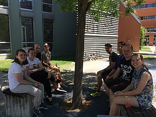 Members of the institute and summer trainees sitting outside on benches.