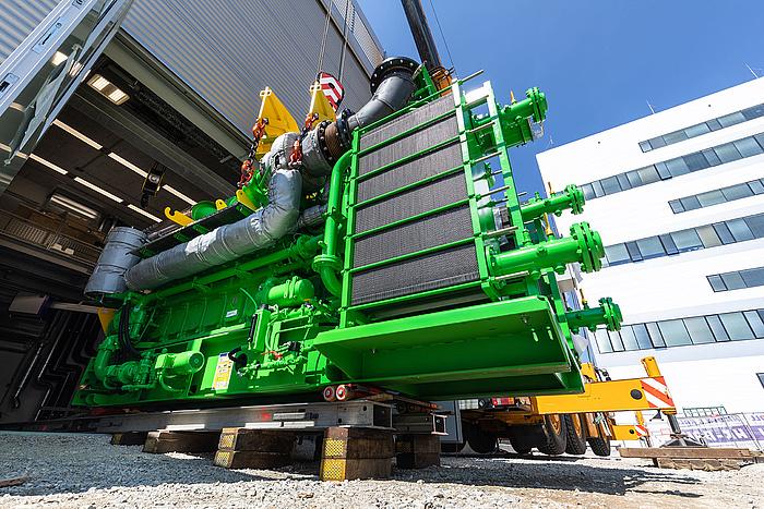 Ein großer, grüner Motor wird in eine Halle gehoben.