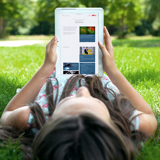 Young woman lying on the lawn looking at her tablet and a page of the TU Graz website. Photo source: BillionPhotos.com - fotolia.com