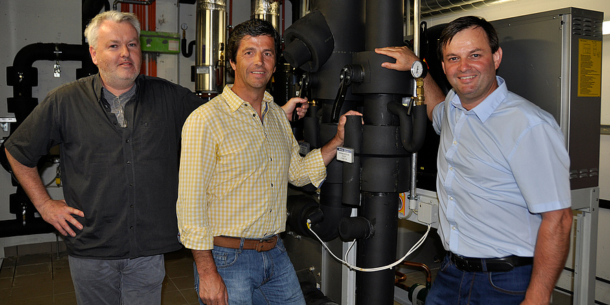 Gernot Prem, Horst Gangl and Siegfried Pabst standing next to the cooling system.
