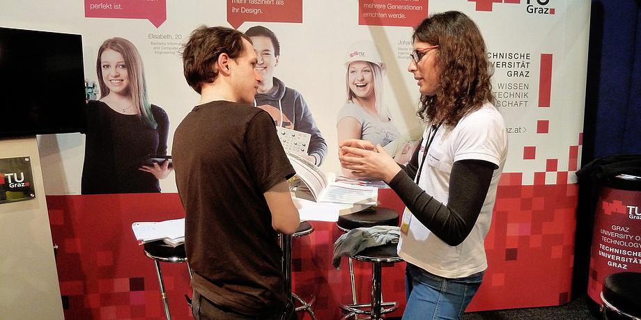 Am TU Graz-Infostand auf der Messe für Beruf, Studium und Weiterbildung in Wien sind eine junge Frau einen Interessent ins Gespräch vertieft.