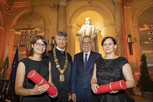 Zwei Frauen und zwei Männer stehen nebeneinander, die beiden Frauen halten rote Rollen in der Hand.
