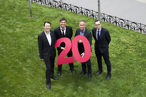 "Four men holding big red figures saying ""2"" and ""0""."
