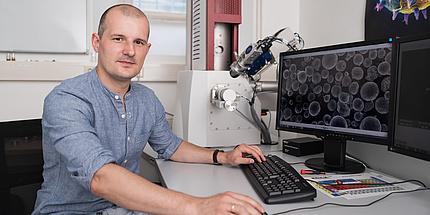Ein Mann mit blauem Hemd sitzt vor einem Bildschirm, auf dem eine Mikroskop-Aufnahme eines Metallpulvers - viele runde Bälle - zu sehen ist
