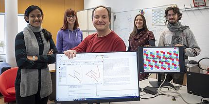 Die Arbeitsgruppe von Oswin Aichholzer steht in einem Büro. Vor ihnen sind zwei Bildschirm mit mathematischen Zeichnungen zu sehen.