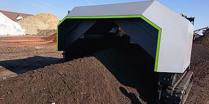 Komposthaufen, der von einer Maschine überfahren wird