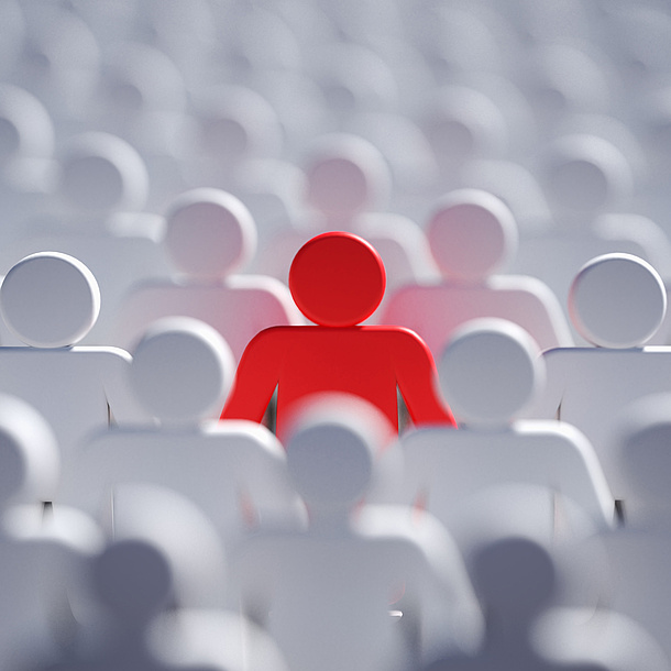 A red human figure in the middle of white human figures. Source: vchalup – Fotolia.com