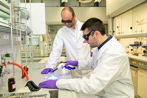 Two men in lab coats and protective goggles, one holding a small light source to a glass object.