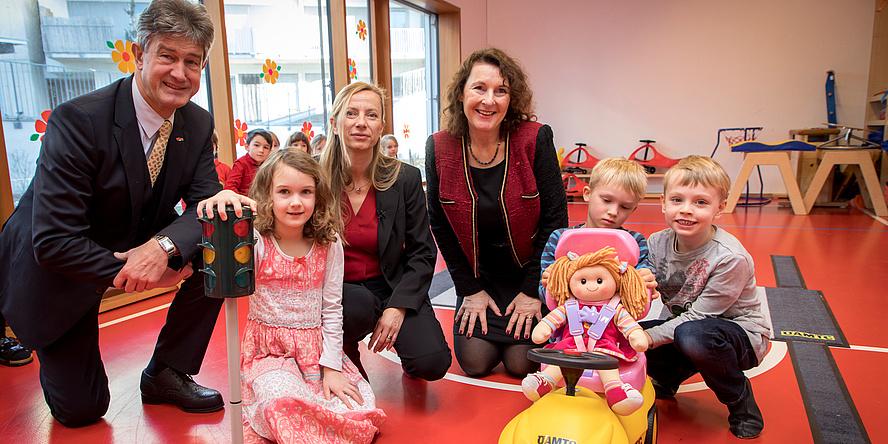 Drei Erwachsene und drei Kinder umgeben von Spielsachen im Turnsaal einer Kinderbetreuungseinrichtung