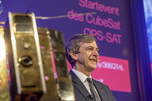 Ein Mann und das Modell des Nanosatelliten OPS SAT