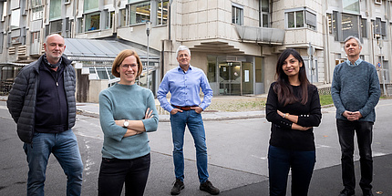 Personengruppe steht vor einem futuristischen Gebäude