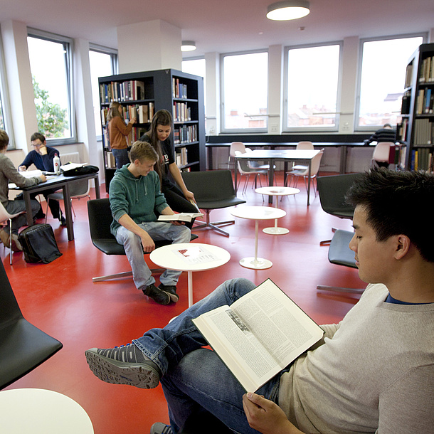 Young people in a room. Some are sitting and reading, others are standing at bookshelves or conversing.