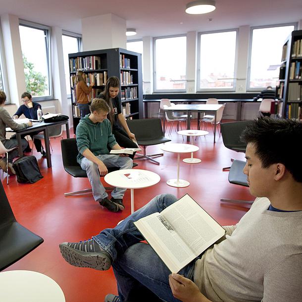 Junge Leute in einem Raum. Ein paar sitzen und lesen in Büchern, andere stehen an Bücherregalen oder unterhalten sich.