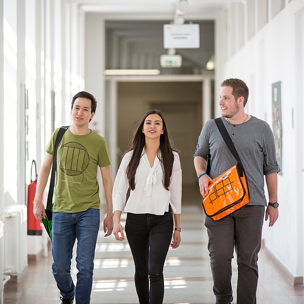 3 students walking along a corridor at TU Graz.