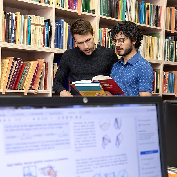 Zwei Männer stehen vor einem Bücherregal und schauen in ein Buch.