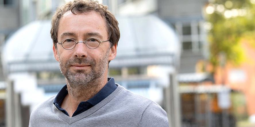 Mann mittleren Alters vor Biotechnologie-Gebäude der TU Graz