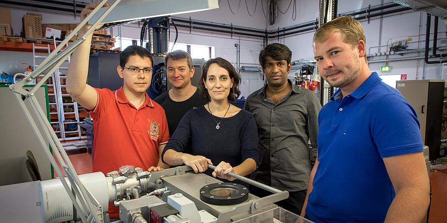 Fünf Personen blicken in die Kamera. Vier davon sind Männer, eine eine Frau. Vor ihnen liegen viele metallische Gegenstände auf einem Tisch.