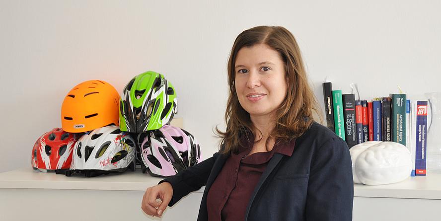 Corina Klug in ihrem Büro. Im Hintergrund sind Fahrradhelme und Bücher zu sehen.