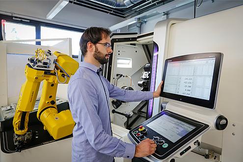TU Graz researcher operates a CNC turning, milling and gear cutting centre