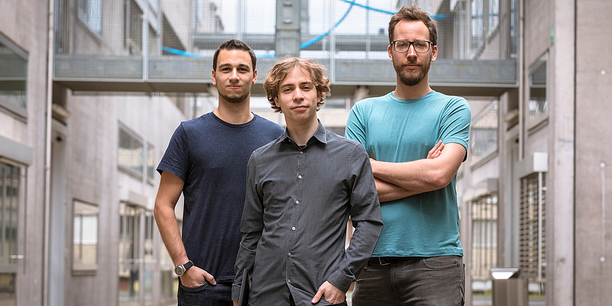 Drei Männer stehen in lockerer Pose im Freien. Links und rechts Betonwände, über Ihnen verbindet eine Glasbrücke die beiden Häuser