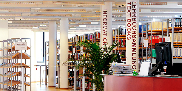Bookshelves and a service counter with a computer in a large room. One column is marked INFORMATION and another is marked LEHRBUCHSAMMLUNG.