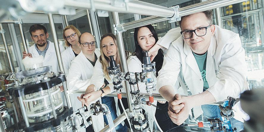 Sechs Forschende in Labormänteln lehnen sich an eine Konstruktion aus Metallstäben in einem Labor.
