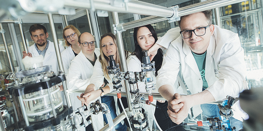 Six researchers in lab coats are leaning against a construction of metal rods in a lab at TU Graz.