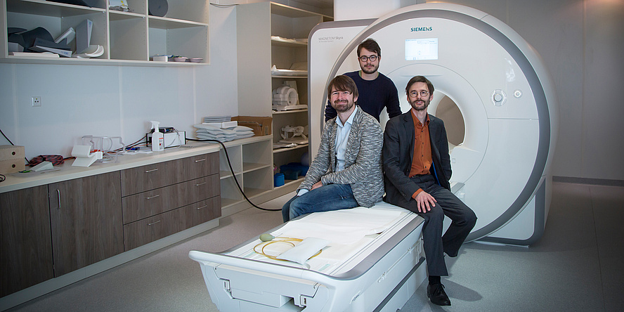 Three gentlemen sit in front of an MRI examination tube on the corresponding couch.