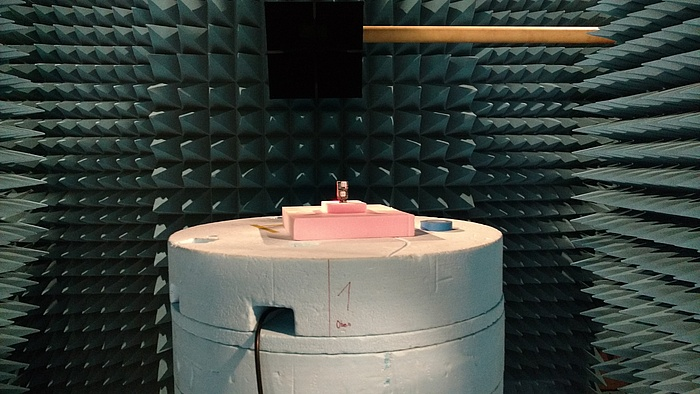 A room lined with blue foam spikes. A pink cylinger sits in the middle of it.