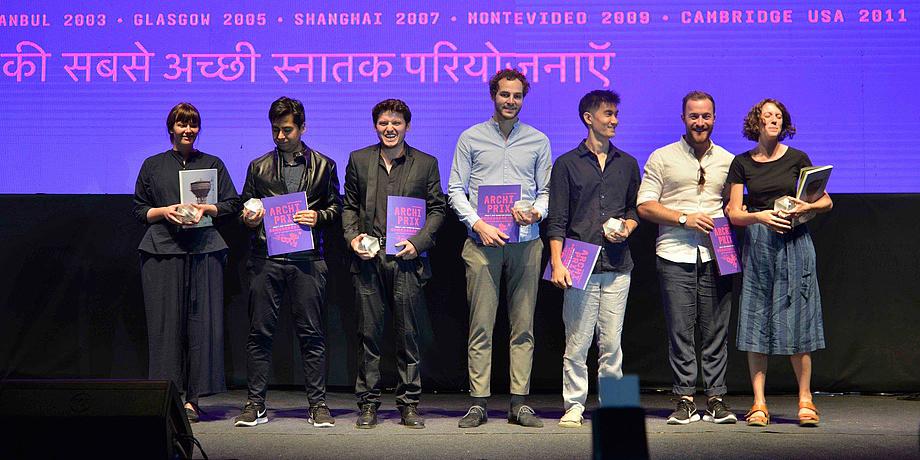 """2 junge Frauen und 5 junge Männer unterschiedlicher Nationalitäten bei der Verleihung des Archiprix mit Urkunden vor einer violetten Wand mit der Aufschrift """"World's best graduation projects. Ahmedabad 2017""""."""