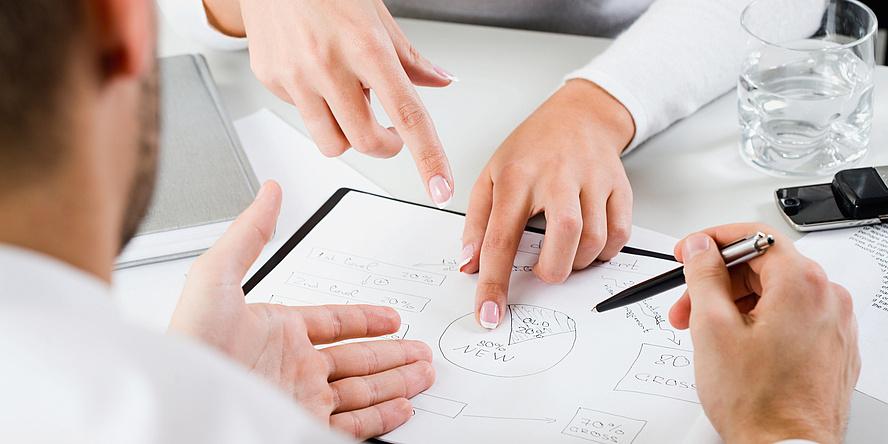 Zwei Personen sitzen sich gegenüber und besprechen ein auf Papier gezeichnetes Kreisdiagramm. Zu sehen sind im Bildausschnitt nur die Hände der Personen und das Diagramm, eine Person hält einen Kugelschreiber in der rechten Hand.