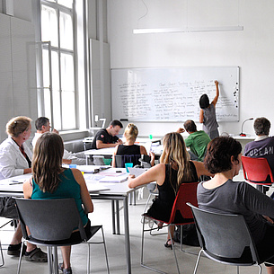 Lecture room with people and a lecturer writing on a black board. Photo source: TU Graz