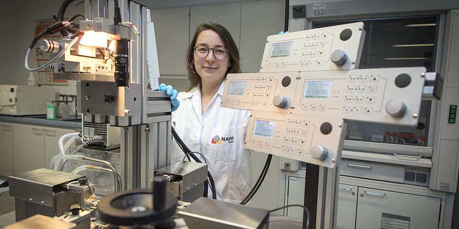 A young woman in a lap coat stands inside a laboratory. Complicated testing equipment surrounds her.