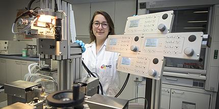 Eine junge Frau steht in einem weißen Mantel in einem Labor. Um sie herum stehen mehrere, komplizierte Geräte.