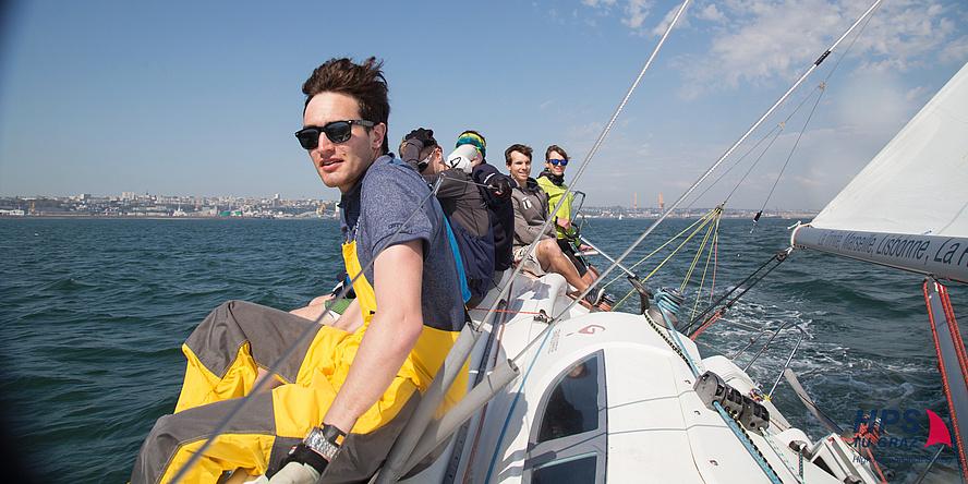 Sechs junge Seglerinnen und Segler sitzen aufgereiht auf einem Segelboot in Schräglage.