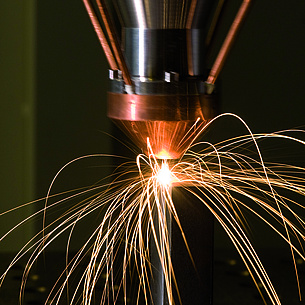 Laser cutter with flying sparks.