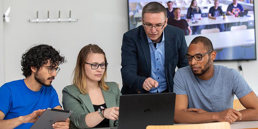 Zwei junge Männer,  einer davon mit Tablet und junge Frau vor einem Laptop sitzend und ein älterer Mann im grauen Anzug hinter ihnen stehend in einer Lernsituation.