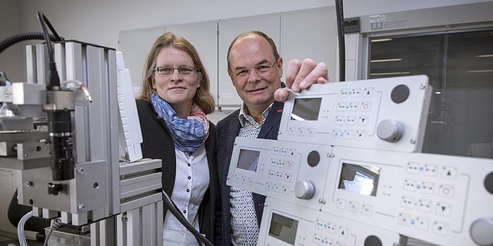 Ein Mann und eine Frau stehen vor medizinischen Geräten.